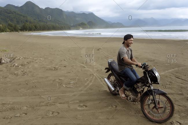 January 29, 2018: Cheerful smiling Asian man on motorcycle on beach, Banda Aceh, Sumatra, Indonesia