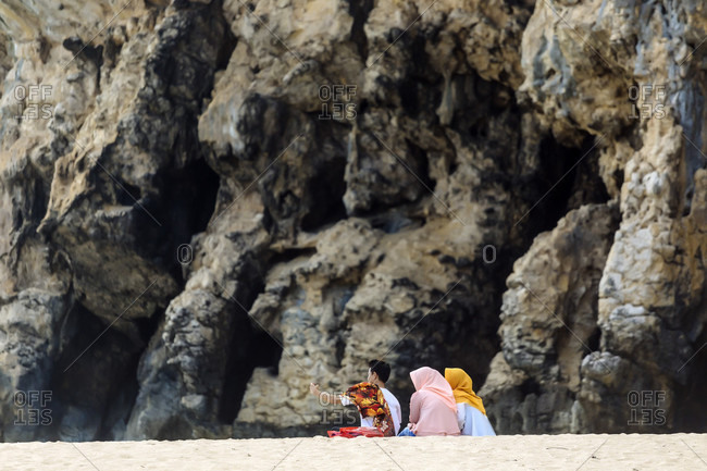 January 31, 2018: Small group of three people sitting on beach against mountain, Banda Aceh, Sumatra, Indonesia