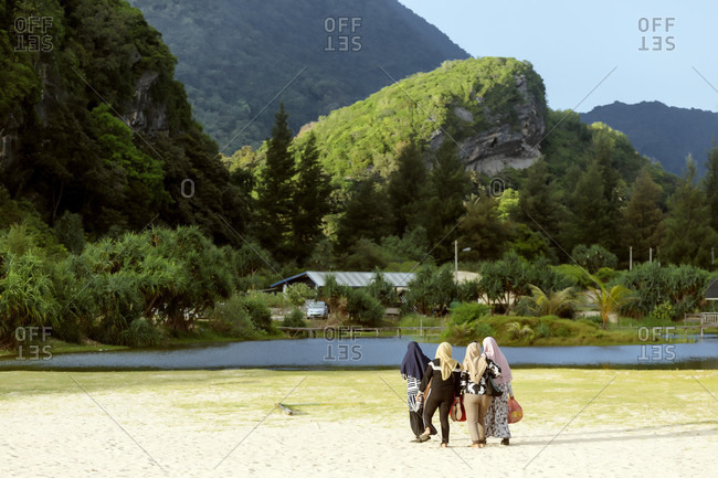 January 31, 2018: Rear view of group of four women in hijabs walking on lakeshore with mountains in background, Banda Aceh, Sumatra, Indonesia