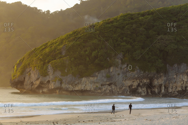 January 31, 2018: Scenic view of two men on beach and mountains, Banda Aceh, Sumatra, Indonesia