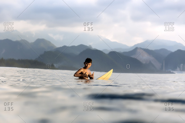 February 1, 2018: Young surfer showing thumbs up in sea