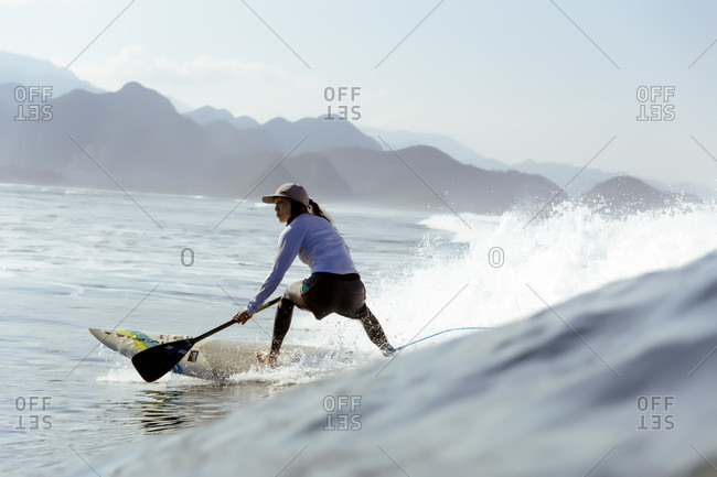 February 2, 2018: Side view shot of single woman paddle surfing in sea