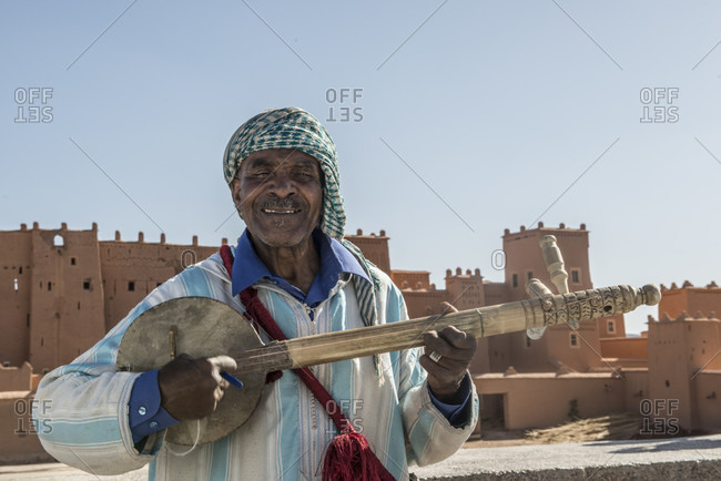 April 6, 2018: Waist up shot of local Berber man playing stringed instrument for tourists in Morocco