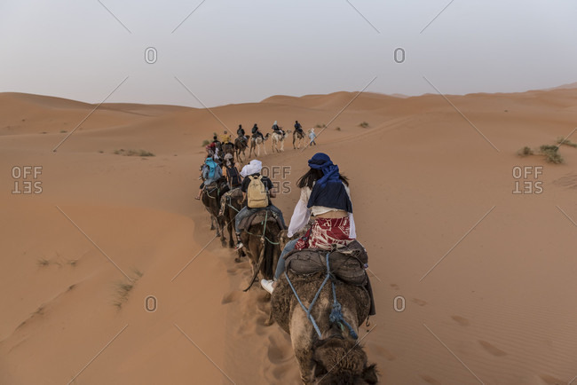 April 5, 2018: Tourists riding camels in Sahara Desert, Merzouga, Morocco