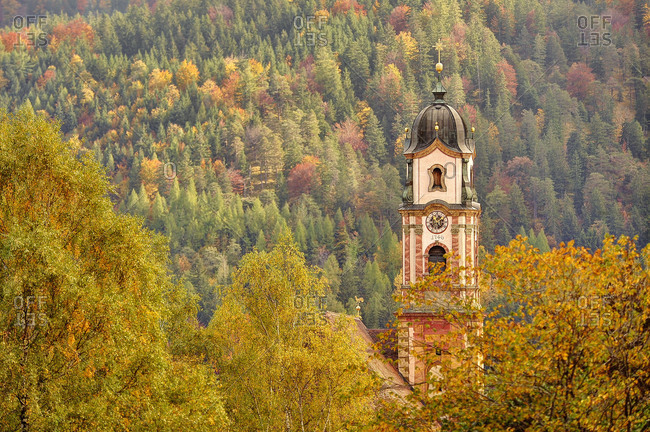 The steeple of Mittenwald in the autumn foliage