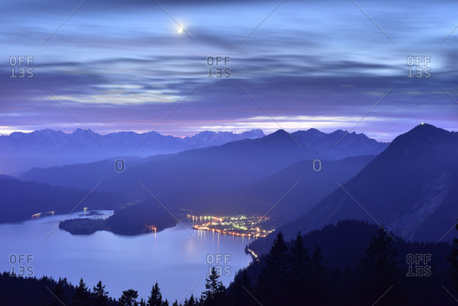 Night photography with dragging clouds and half moon of the Walchensee and the adjacent mountains, behind it the Wetterstein Range with Zugspitze.