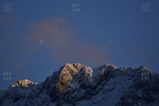 The western Karwendelspitze with summit cross in the last wintry evening light, alpenglow with light clouds.