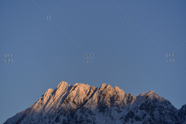 The Karwendel in the last light of a wintry day, with blue heaven with snow.