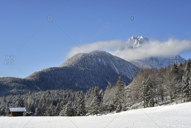View over Mittenwald to the Wetterstein over a snow-covered meadow with hay stack.