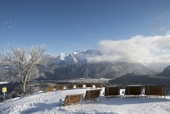 Sun bed in winter on the Kranzberg, in the background the Karwendel with clouds and the violin maker town Mittenwald.