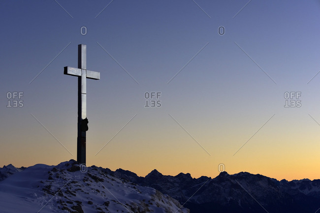 Evening sun at the summit of the Heimgarten, summit cross shines silver.