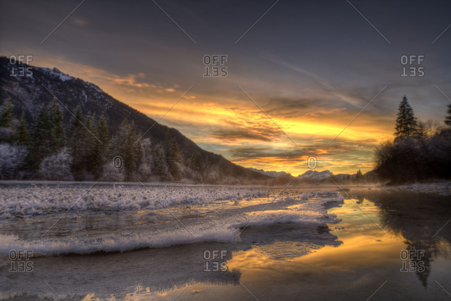Spectacular sundown in the Isar meadows near Wallgau. In the foreground fine ice structures, in the background  in distance the Wetterstein Range with Zugspitze.