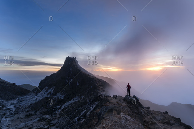Mountaineer watches the foggy sunrise in mountain Siabayak, a volcano on the Indonesian island Sumatra
