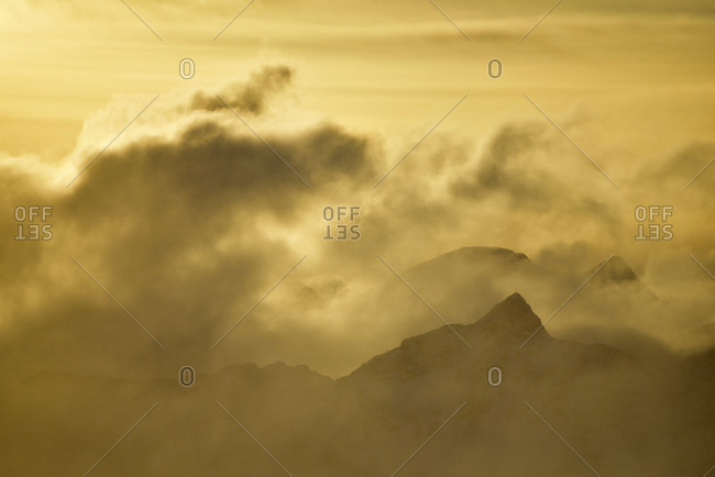 View from the Herzogstand on a sea of clouds and some silhouettes of mountaintops in the golden evening light.