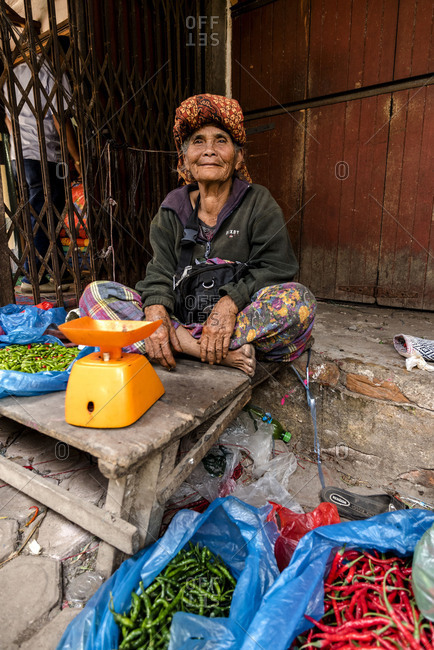 Very old market woman offers chilli pods.