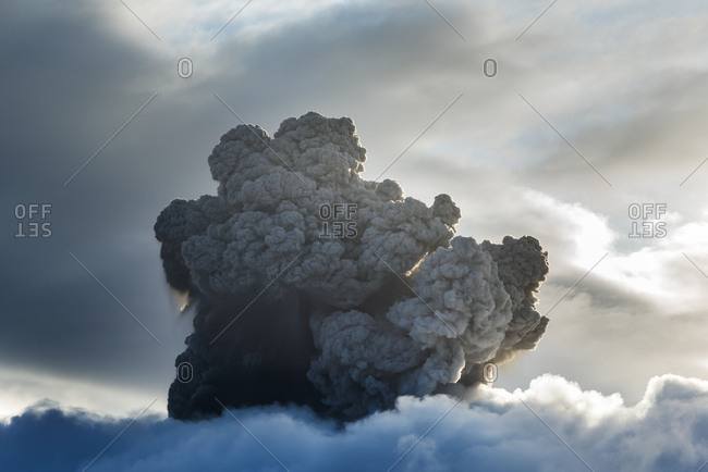 pyroclastic cloud of a volcano eruption of the Mt. Sinabung on Sumatra in Indonesia, rises dramatically over the cloud cover