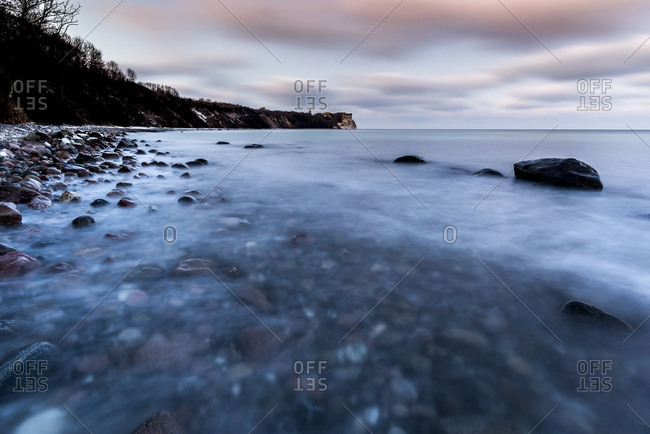 Long time exposure in the evening light of the wintry steep coast in cape Arkona on Rugen. In the foreground the water of the Baltic Sea and several big stones, in the background the steep coast with the small lighthouse and special clouds.