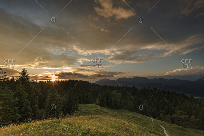 View from the Kranzberg at Mittenwald, as the setting sun with sunrays and nice beautiful clouds. A small path writhes in the direction of edge of the forest and the sun, in the foreground a flower meadow
