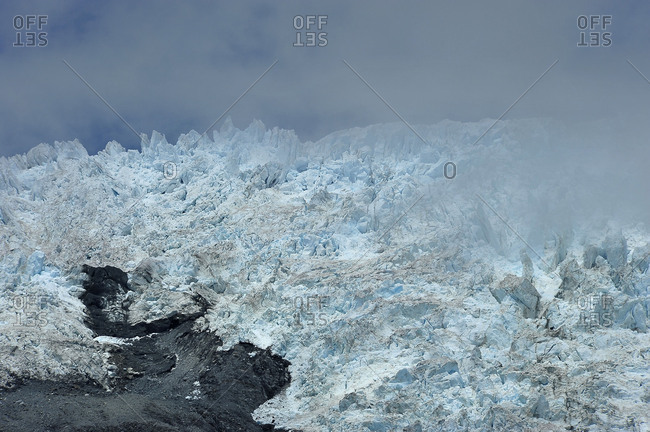 Parts of the fox glacier in New Zealand with low clouds