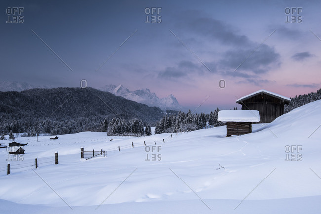 Two wood barns in the hamlet Gerold during wintry sunrise. In the background is the Zugspitze.