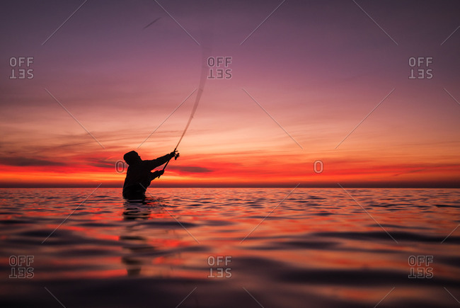 Angler casts her hinge during sundown.