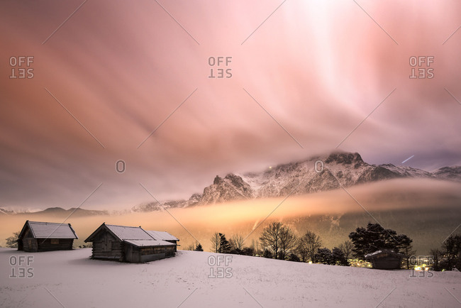Night photography of the Karwendelgebirge (mountains) in winter, with snow and wooden hut in the foreground. Nebulous mood by the lights of the market Mittenwald illuminated, while the clouds seem strip-type over the mountains by the long time exposure.