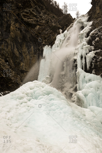 In the frozen and iced up Gossnitz waterfall water falls down.