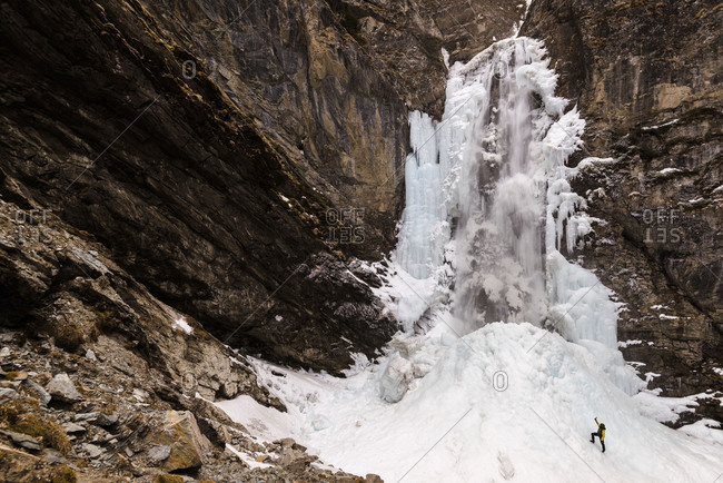 Young woman films the iced up Gossnitz waterfall in Hohe Tauern with camera.