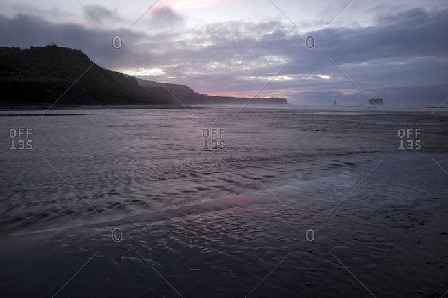 Course of a river on a beach in New Zealand during mauve sundown, steep rocks rise in the background.