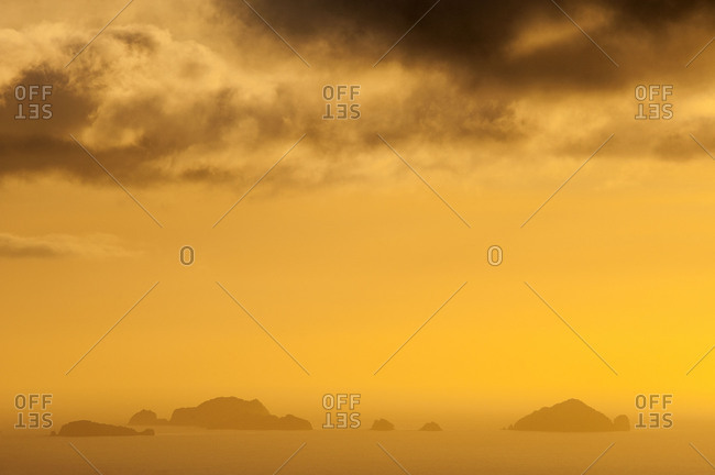 Small islands on the New Zealand coast of Coromandel during a golden light mood with dark clouds.