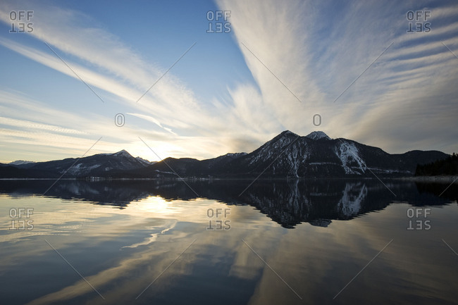 Mirroring in the Walchensee. Sundown and special cloud formation are reflected in the Walchensee in front of the silhouette of the Herzogstand and Simetsberg.