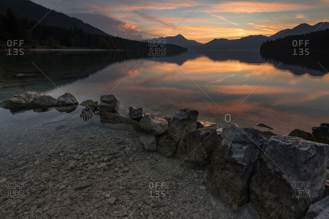 Stones on the shore of the Walchensee during sundown and gathering storm over the mountains in the background