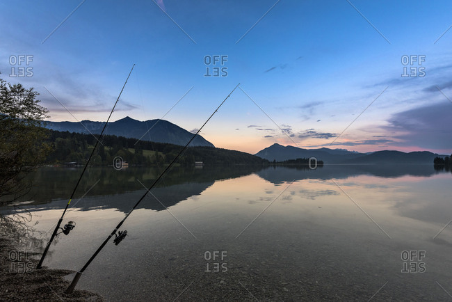 Two fishing rods in the dusk in the crystal-clear Walchensee, in the background peninsula Zwergern, Herzogstand and Jochberg.