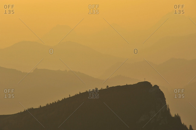 View from the Benediktenwand on a small mountaintop with summit cross in orange evening light.