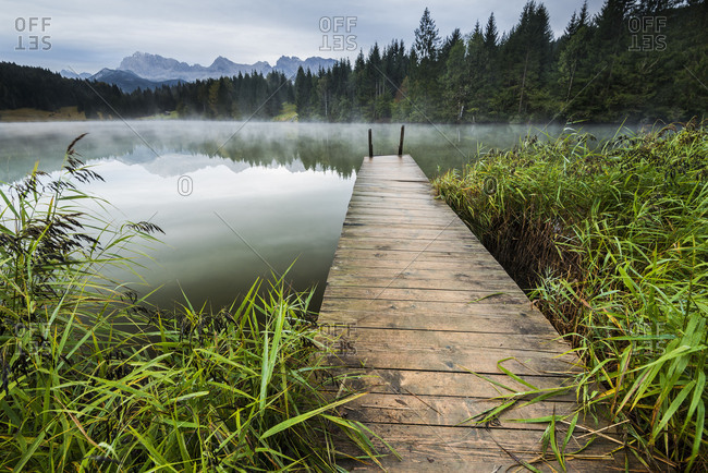 An old wooden jetty between reed in a small mountain lake, in the background fog and the Karwendelgebirge (mountains).