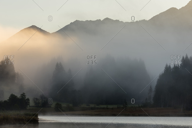 From the early morning sunlight of tinted fog about the rear part of the Geroldsee with Garmisch-Partenkirchen. In the background the silhouette of the alpine Soierngruppe and wood.