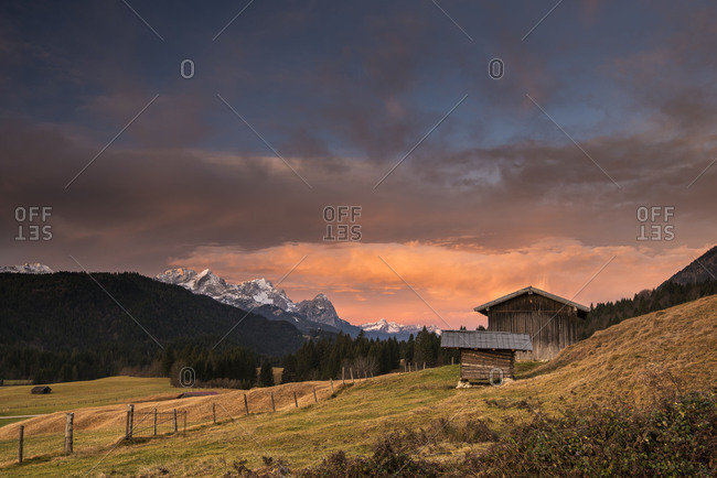 Two mountain huts, or scales in front of an impressive morning mood with Zugspitze in the background.