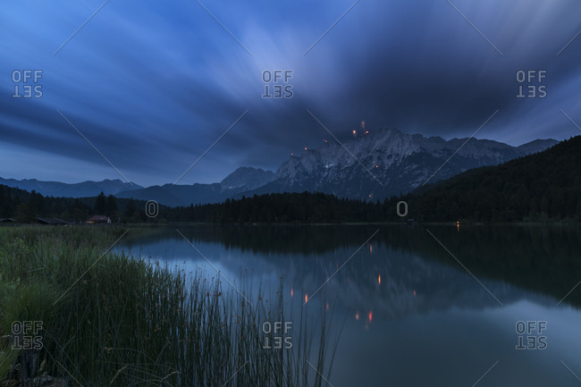 St. John\'s fire and rockets at the western side of Karwendel (mountain) (mountain) over Mittenwald. in foreground the idyllic Lautersee (lake) with reed and forest, over that move cloud veils resulted by long time exposure