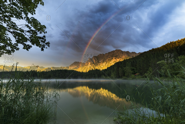 A rainbow in the golden evening light. Alpenglow at the western side of Karwendel (mountain) (mountain) over Mittenwald illuminate the mountains, while in foreground fog from the Lautersee (lake) rises up
