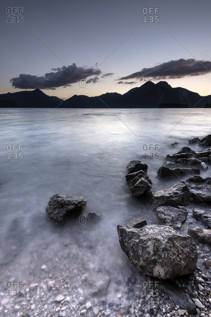 Shortly after Sundown at the Walchensee (Lake Walchen), over the  Fahrenberg (mountain) or Herzogstand (mountain) and the Simetsberg (mountain) are two clouds waves in foreground, stone structures