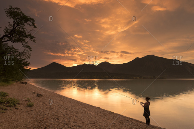 Young woman fishes on the shore of the Walchensee / Lake Walchen while dramatic sundown