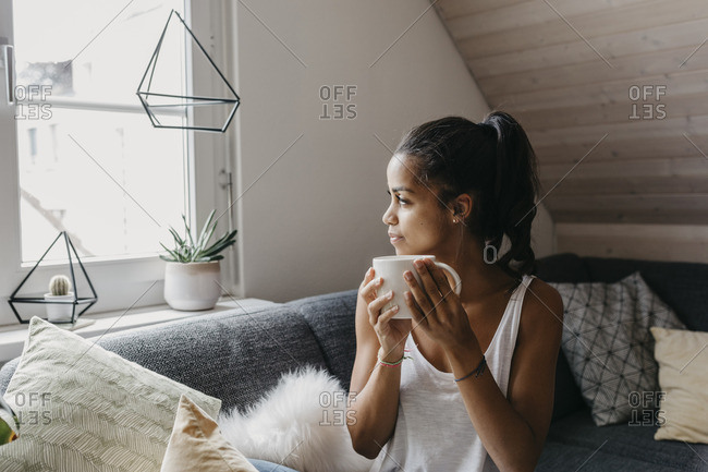 Young woman with cup of coffee sitting on the couch at home looking out of window