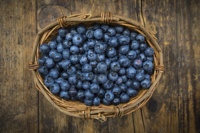 Wicker basket of blueberries on wood