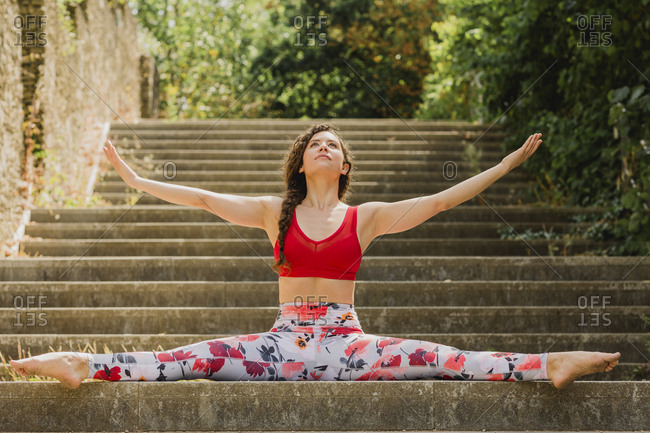Young woman practicing Pilates in an urban park- spagat on steps