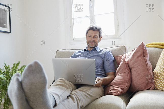 Man sitting on couch at home- using laptop