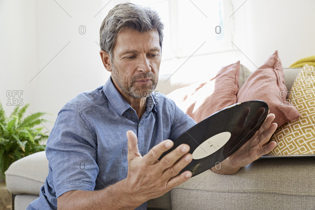 Mature man at home sitting in front of couch- looking at old vinyl record