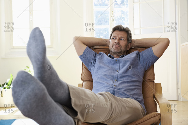 Man sitting in arm chair with feet up- daydreaming