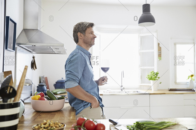 Mature man in his kitchen tasting red wine