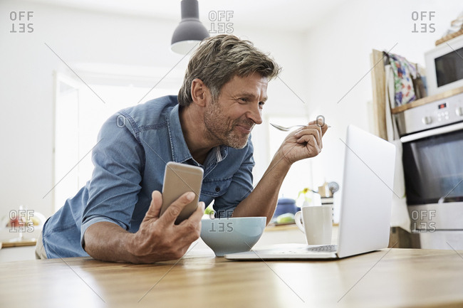 Mature man in his kitchen having breakfast- while checking his laptop