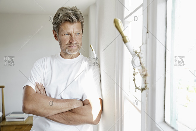 Mature man standing by window with arms crossed
